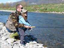 Cheerful father and daughter fishing together on the river Stock Image