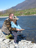 Cheerful father and daughter fishing together on the river Stock Photography
