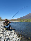 Cheerful father and daughter fishing together on the river Stock Photo