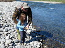 Cheerful father and daughter fishing together on the river Stock Photos