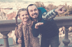 Cheerful father and daughter pointing at sight during sightseein Stock Images