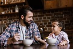 cheerful father and daughter sitting at table and eating snacks with milk stock image