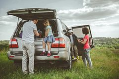 Friendly family preparing for journey near car. Cheerful father and daughter are taking baggage from the car trunk. Mother is helping her son to going out the Stock Photos