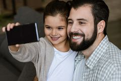 cheerful father with daughter taking selfie on smartphone royalty free stock photography