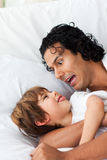 Cheerful father having fun with his son. Lying on bed Royalty Free Stock Photography