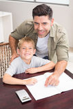 Cheerful father helping son with his math homework at table Stock Images