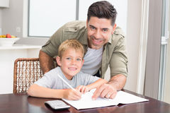 Cheerful father helping son with math homework at table Royalty Free Stock Photography