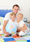Cheerful father and his children holding a globe Royalty Free Stock Photos