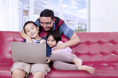 Cheerful father and his children watch a movie Royalty Free Stock Image