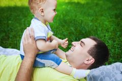 Cheerful father and his son on grass. Cheerful father and his son playing on grass, young men lying on coverlet and holding his child in his arms Royalty Free Stock Photography