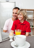 Cheerful father and his son having breakfast Royalty Free Stock Images
