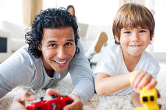 Cheerful father and his son playing video games. Lying on the floor in the living-room Stock Photo