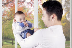 Cheerful father holds his cute baby Stock Images