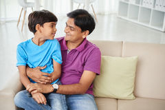 Cheerful father and kid. Indian boy sitting on knees of his father Stock Images