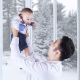 Cheerful father with male baby at home Royalty Free Stock Photos