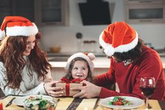 Cheerful father and mother giving present to their daughter stock photo