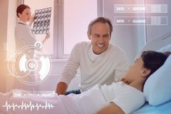 Cheerful father smiling to his child while a nurse standing near stock photos