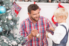 Cheerful father and son are decorating Christmas. Cute men and boy are ready to decorate New Year tree. They are standing and holding toy spheres. The men is royalty free stock images