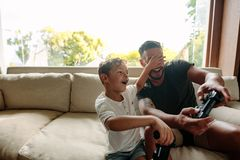 Cheerful father and son enjoying playing video game. Little boy covering eyes of his father playing video game. Cheerful family of father and son having fun Royalty Free Stock Image