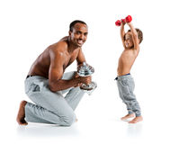 Cheerful father and son exercising with dumbbells and smiling Royalty Free Stock Image