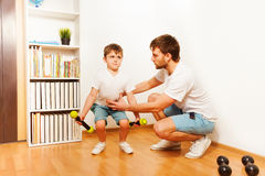 Cheerful father and son exercising with dumbbells Stock Photography