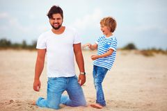 Cheerful father and son, family having fun, playing on summer beach. Cheerful father and son, happy family having fun, playing on summer beach Stock Photos