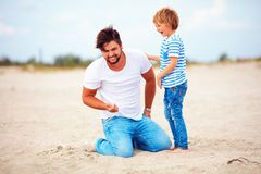 Cheerful father and son, family having fun, playing on summer beach. Cheerful father and son, happy family having fun, playing on summer beach Royalty Free Stock Photography
