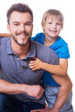 Cheerful father and son. Happy little boy embracing his father and smiling while both standing isolated on white stock image