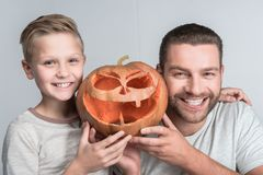 Father and son with halloween pumpkin. Cheerful father and son holding halloween pumpkin and smiling at camera isolated on grey royalty free stock photo