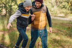 Cheerful father and son holding hands while walking together. In autumn forest Royalty Free Stock Image