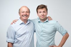 Cheerful father and son hugging and posing together. Isolated on white background. Man is proud of his friend stock photography