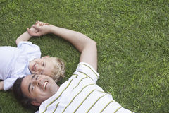 Cheerful Father And Son Lying On Grass Royalty Free Stock Photos