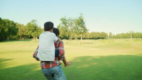 Father and son playing together in park. Man running on green field with boy
