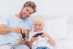 Cheerful father and son playing video games Stock Images