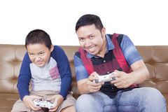 Cheerful father and son playing video games. Portrait of cheerful father and his son playing video games while sitting on the sofa, isolated on white background royalty free stock photos