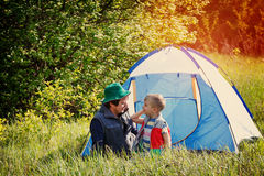 Cheerful father and son sitting near the tent while camping in the forest Royalty Free Stock Photo