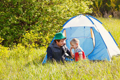 Cheerful father and son sitting near the tent while camping in the forest. Cheerful father and son sitting near the tent while camping in forest Stock Images