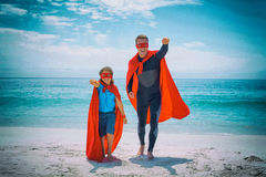 Cheerful father and son in superhero costume with hand raised Stock Photo