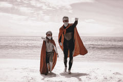 Cheerful father and son in superhero costume with hand raised Stock Image