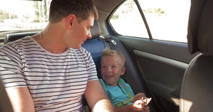 Cheerful father and son traveling by car. Happy little boy with toy and backpack traveling with young father on the backseat of a car. They having cheerful talk stock footage
