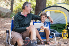 Cheerful father and son using digital tablet in forest Royalty Free Stock Photography
