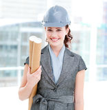 Cheerful female architect with hard hat and plans. Standing in a modern building Stock Image