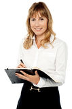 Cheerful female assistant writing notes Royalty Free Stock Image