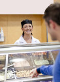 Cheerful female baker listening to a student Stock Photo