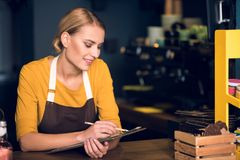 Cheerful female barista noting document in cafe. E view beaming woman writing information while working in confectionary shop. Job concept Royalty Free Stock Photography