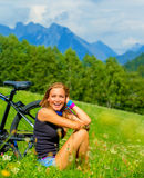 Cheerful female with bicycle on green field royalty free stock photography