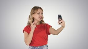 Cheerful female blogger recording video to front camera of modern telephone while walking on gradient background. royalty free stock photo