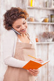 Cheerful female cafe worker is making notes Royalty Free Stock Images