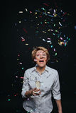 Cheerful female with champagne in confetti Royalty Free Stock Photo