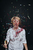 Cheerful female with champagne in confetti Royalty Free Stock Photography